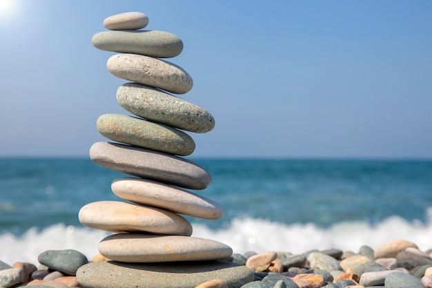 바다 배경에 매끄러운 돌 피라미드의 균형을 맞 춥니 다. 사물의 균형과 생활 수준.