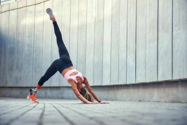 Баланс и гибкость в полной мере молодой женщины-инвалида с протезом ноги в спортивной одежде делают