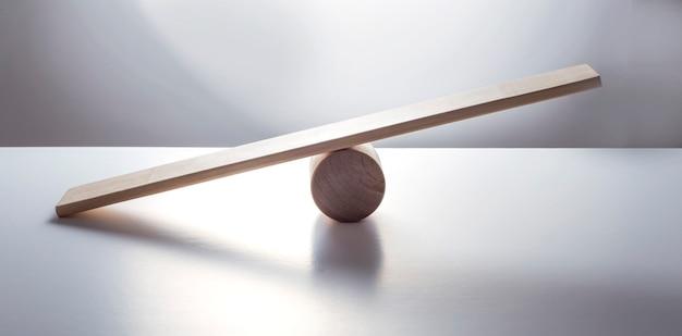 Концепция баланса, доска на деревянном цилиндре, как баланс, изолированные на белой поверхности
