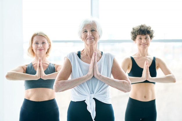 Balance and energy. women group meditating next to a large window