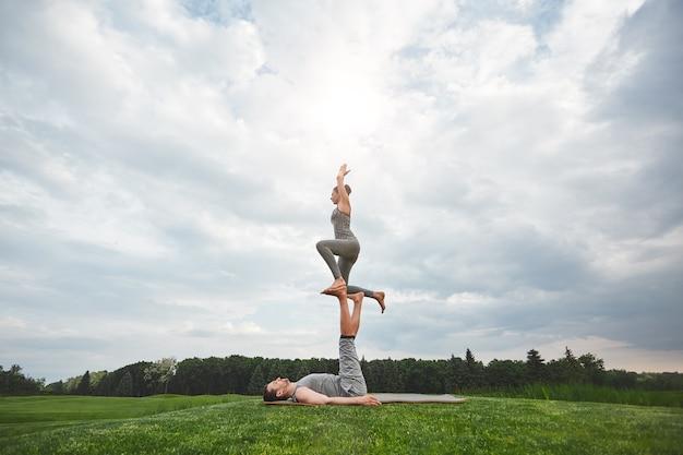 균형 운동은 건강하고 젊은 부부가 누워 자연 속에서 곡예 요가를 하는 강한 남자