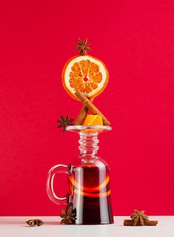 Balance는 계피, 오렌지 및 스타 아니스와 함께 빨간색 배경에 거꾸로 된 유리에 담긴 뜨거운 와인입니다. mulled 와인 세트 중 하나입니다.