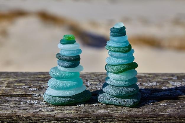 石のバランス。海に対して木製のテーブルの上のガラスの石。 2つのピラミッド