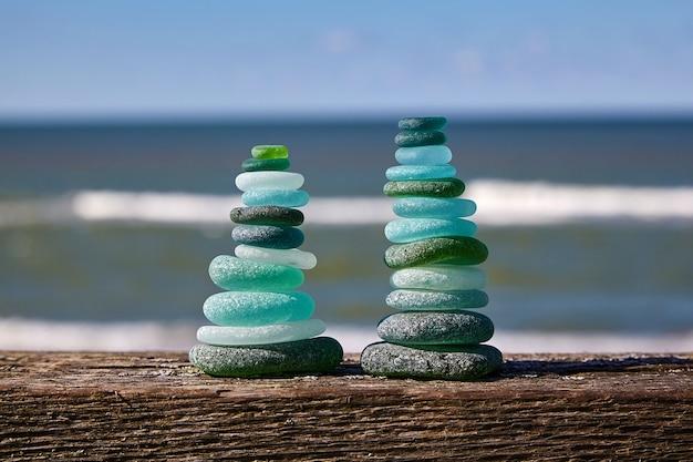石のバランス。海に対して木製のテーブルの上のガラスの石。 2つの塔