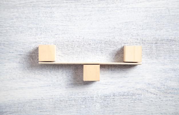 木製の立方体から作られたバランススケール。