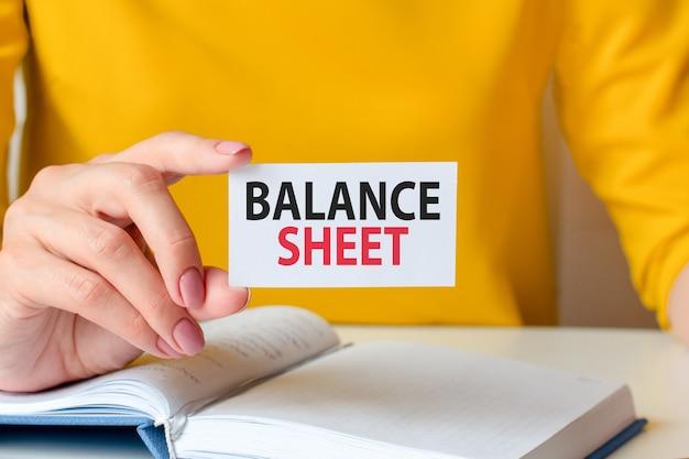 貸借対照表は白い名刺に書かれています。女性の手は、黄色のドレスと白いノートを背景に白い紙のカードを持っています。ビジネスと広告の概念。