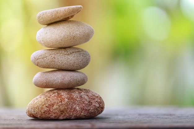 Баланс камня на деревянном полу и мягкий солнечный свет в саду.