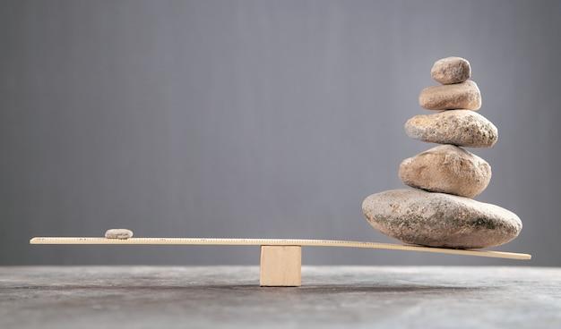 木製のはかりで石のバランスを取ります。