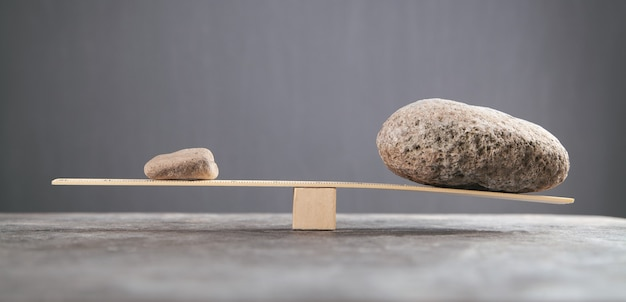 Balance stones on wooden scales.