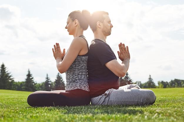 Сбалансируйте свою жизнь молодая пара, медитируя вместе, сидя в позе лотоса, спиной к
