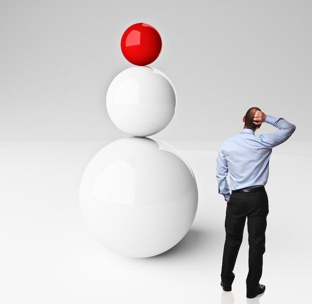 Сбалансированные шары и думающий человек, изолированные на белом фоне