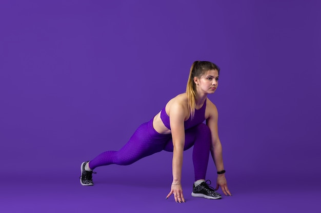Balanced. beautiful young female athlete practicing in , monochrome purple portrait. sportive caucasian fit model training. body building, healthy lifestyle, beauty and action concept.