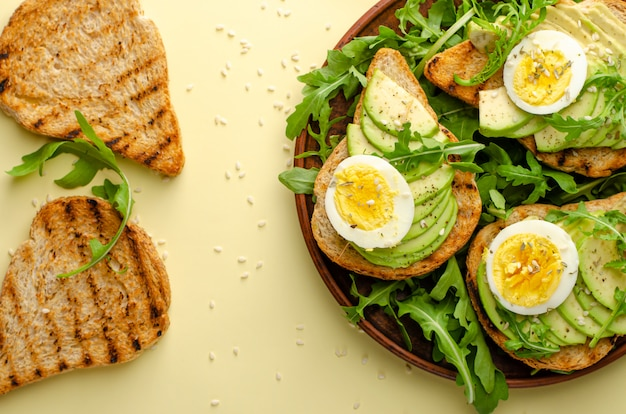 Balanced diet. avocado toasts with egg and arugula salad. overhead, flat lay