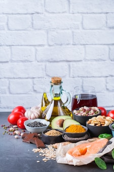 Balanced diet food concept. assortment of healthy food low cholesterol, spinach avocado red wine green tea salmon tomato flax chia seeds turmeric garlic nuts olive oil