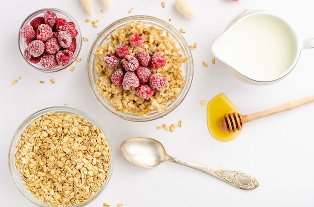Balanced diet food menu for breakfast with oats porridge bowl with raspberries and honey dipper