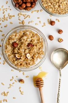 Сбалансированное диетическое меню на завтрак с овсяной кашей, миской с фундуком и медом
