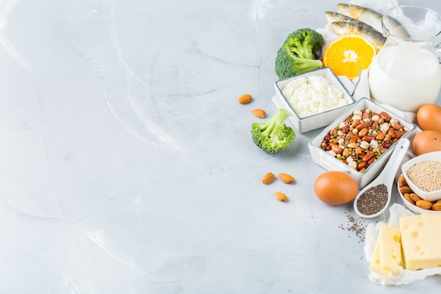 Balanced diet nutrition, healthy eating concept. assortment of food sources rich in calcium, beans, dairy products, sardines, broccoli, chia seeds, almonds on a kitchen table. copy space background