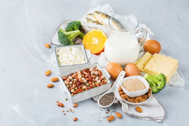 Balanced diet nutrition, healthy eating concept. assortment of food sources rich in calcium, beans, dairy products, sardines, broccoli, chia seeds, almonds on a kitchen table