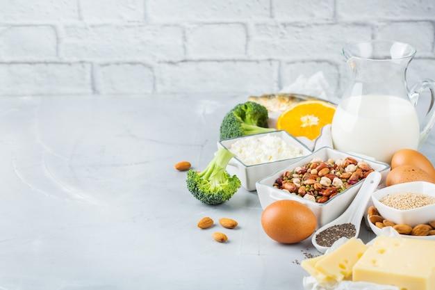 균형 잡힌 식단 영양, 건강한 식생활 개념. 식탁에 있는 칼슘, 콩, 유제품, 정어리, 브로콜리, 치아씨드, 아몬드가 풍부한 다양한 음식 소스. 공간 배경 복사