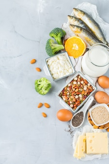 バランスの取れた食事栄養、健康的な食事の概念。カルシウム、豆、乳製品、イワシ、ブロッコリー、チアシード、アーモンドが豊富な食料源の品揃え。スペースの背景をコピーする