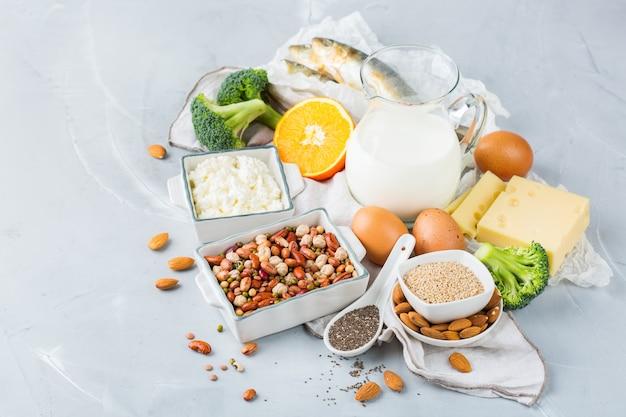 バランスの取れた食事栄養、健康的な食事の概念。カルシウム、豆、乳製品、イワシ、ブロッコリー、チアシード、アーモンドが豊富な食料源の品揃え