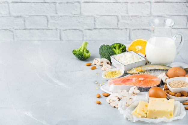 バランスの取れた食事栄養、健康的な食事の概念。キッチンテーブルにあるビタミンdとカルシウム、サーモン、乳製品、イワシ、ブロッコリーが豊富な食品の品揃え。スペースの背景をコピーする
