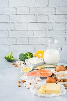 Сбалансированное диетическое питание, концепция здорового питания. ассортимент источников пищи, богатых витамином d и кальцием, лосось, молочные продукты, сардины, брокколи на кухонном столе. скопируйте космический фон