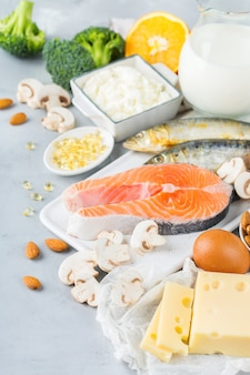 Сбалансированное диетическое питание, концепция здорового питания. ассортимент источников пищи, богатых витамином d и кальцием, лосось, молочные продукты, сардины, брокколи на кухонном столе