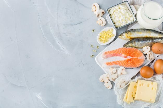 バランスの取れた食事栄養、健康的な食事の概念。ビタミンd、サーモン、乳製品、牛乳、卵、チーズ、きのこ、イワシが豊富な食料源の品揃え。スペースの背景をコピーする