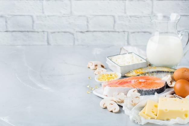 Сбалансированное диетическое питание, концепция здорового питания. ассортимент источников пищи, богатых витамином d, лосось, молочные продукты, молоко, яйца, сыр, грибы, сардины на кухонном столе. скопируйте космический фон