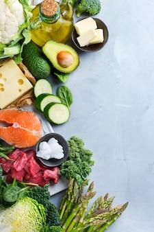Концепция кето питания сбалансированной диеты. ассортимент полезных кетогенных пищевых ингредиентов с низким содержанием углеводов для приготовления на кухонном столе. зеленые овощи, мясо, лосось, сыр, яйца. фон вид сверху