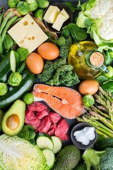 Концепция кето питания сбалансированной диеты. ассортимент здоровых кетогенных пищевых ингредиентов с низким содержанием углеводов для приготовления на кухонном столе. зеленые овощи, мясо, лосось, сыр, яйца. фон вид сверху