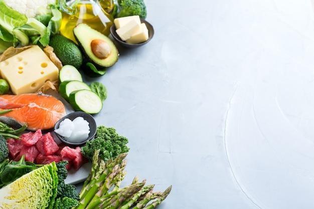 バランスの取れた食事栄養ケトの概念。台所のテーブルで調理するための健康的なケトン体生成低炭水化物食品成分の品揃え。緑の野菜、肉、サーモン、チーズ、卵