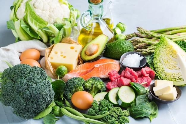 Концепция кето питания сбалансированной диеты. ассортимент здоровых кетогенных пищевых ингредиентов с низким содержанием углеводов для приготовления на кухонном столе. зеленые овощи, мясо, лосось, сыр, яйца