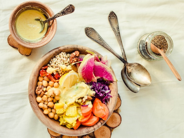 Сбалансированный ужин в деревянной посуде на белой льняной скатерти.
