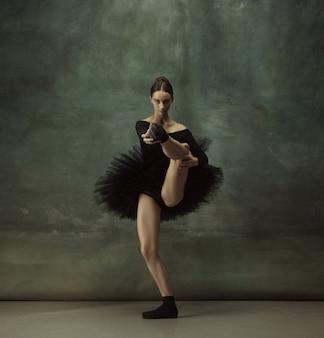 Balanced. graceful classic ballerina dancing, posing isolated on dark studio wall