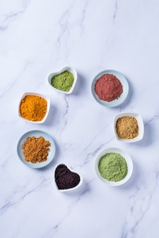 Balanced nutrition concept for clean eating antioxidant detox diet. assortment of superfood powder - acai, turmeric, wheat, ginger, cinnamon, matcha. flat lay, copy space marble background