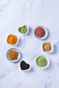きれいに食べる抗酸化デトックスダイエットのためのバランスの取れた栄養コンセプト。スーパーフードパウダーの品揃え-アサイ、ターメリック、小麦、生姜、シナモン、抹茶。フラットレイ、コピースペース大理石の背景