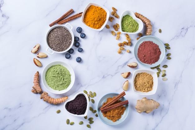 きれいに食べる抗酸化デトックスダイエットのためのバランスの取れた栄養コンセプト。スーパーフードパウダーの品揃え-アサイ、ターメリック、小麦、生姜、シナモン、抹茶。フラットレイ大理石の背景 Premium写真