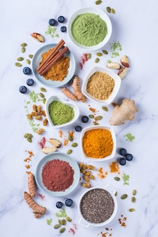 きれいに食べる抗酸化デトックスダイエットのためのバランスの取れた栄養コンセプト。スーパーフードパウダーの品揃え-アサイ、ターメリック、小麦、生姜、シナモン、抹茶。フラットレイ大理石の背景