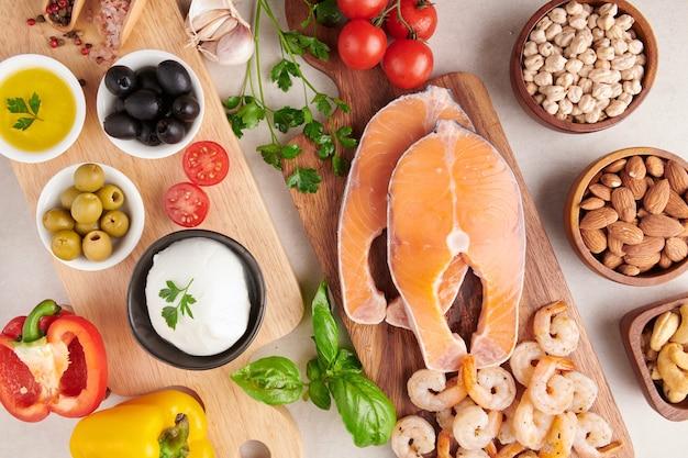 クリーンな食事のフレキシタリアン地中海ダイエットのためのバランスの取れた栄養コンセプト上面図フラット。栄養、きれいな食事の食品の概念。ビタミンとミネラルを使ったダイエットプラン。鮭とエビ、野菜を混ぜる