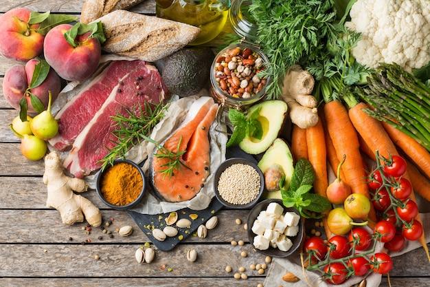 準菜食主義の地中海式食事をきれいに食べるためのバランスの取れた栄養の概念。台所のテーブルで調理するための健康的な食材の品揃え。上面図フラットレイ背景