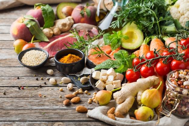 準菜食主義の地中海式食事をきれいに食べるためのバランスの取れた栄養の概念。木製のキッチンテーブルで調理するための健康的な食材の品揃え。