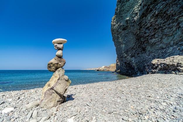 晴れた日のビーチと日没の澄んだ空のバランスの取れた小石のピラミッド。