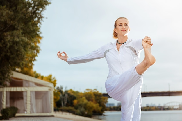 Balanced pose. calm and confident woman standing on the one leg