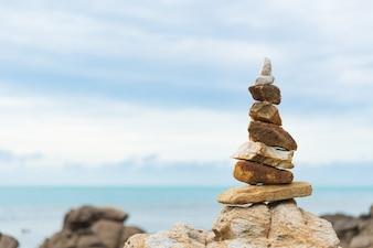 Balanced stone pyramid on water of ocean. life balance concept.