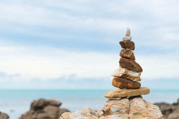 Сбалансированная каменная пирамида на воде океана. концепция баланса жизни.