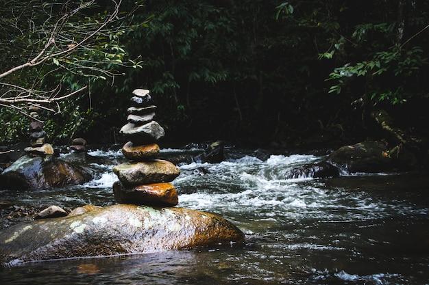 山の湖の滝の岸にバランスの取れた石ピラミッド。水面鏡の青い山。照明条件が悪い。