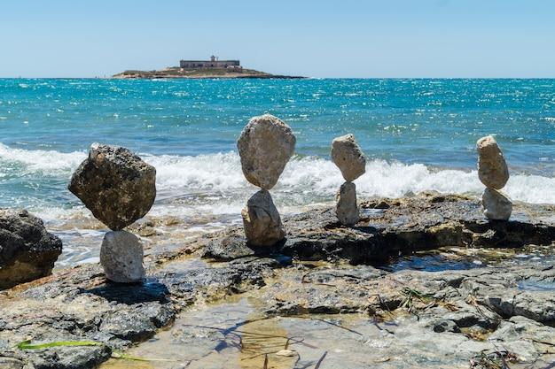 Сбалансированные камни возле острова течений на сицилии