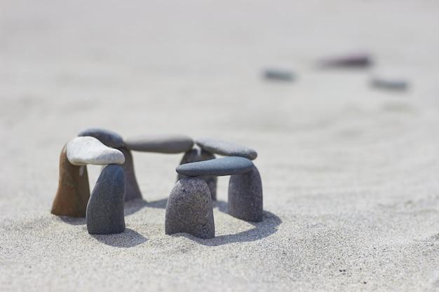 Сбалансированные камни на песке. маленький стоунхендж